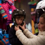 Natalie helps Seth try on a helmet for size.