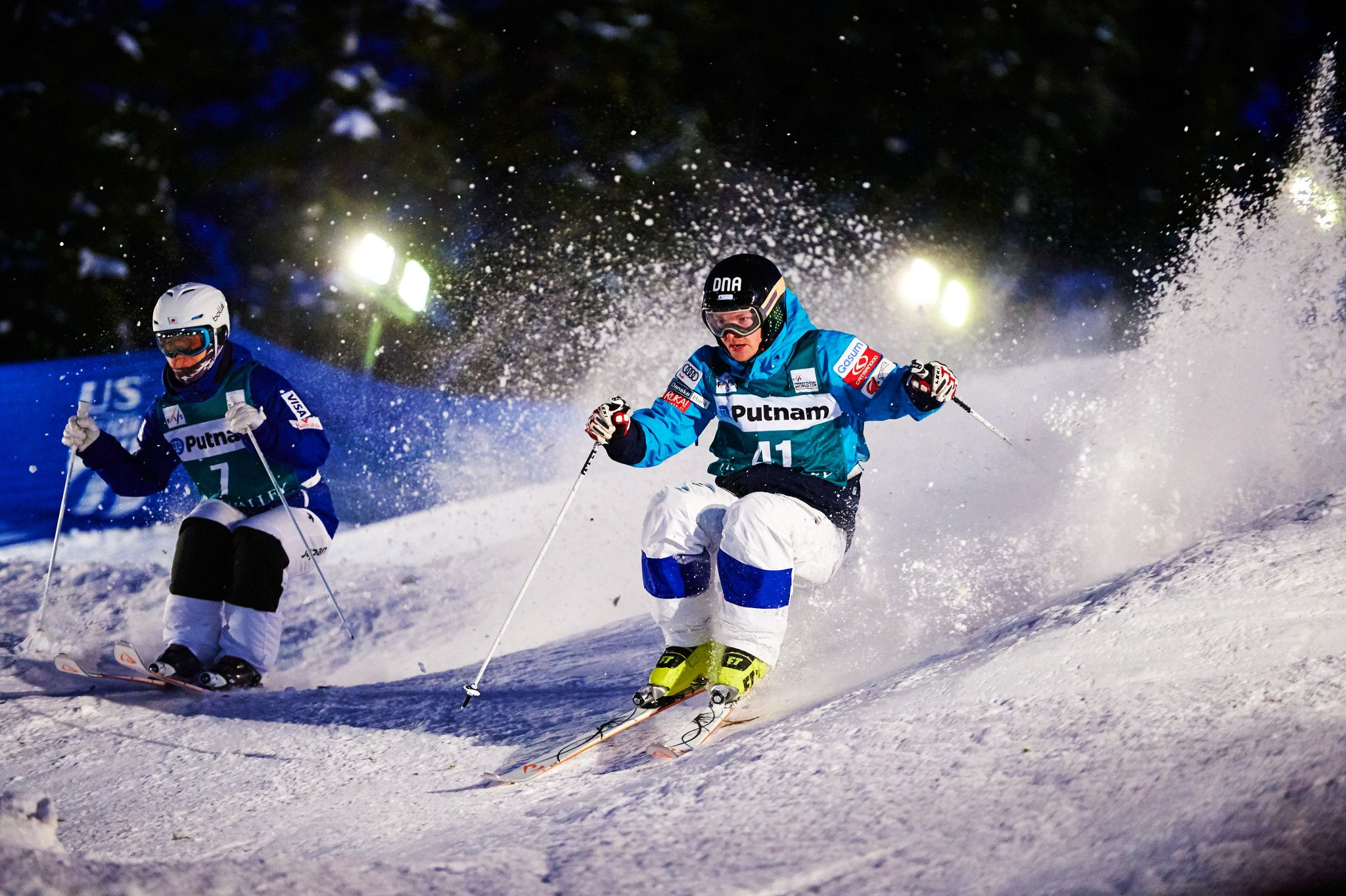 Two male skiers racing down Champion Ski Run at Deer Valley Resort.