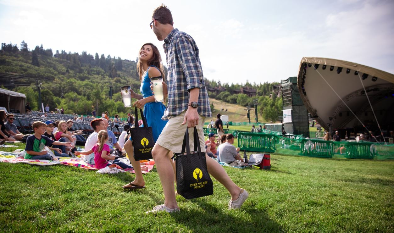 Guests walking with picnic baskets at a concert at Deer Valley Resort in Park City, Utah