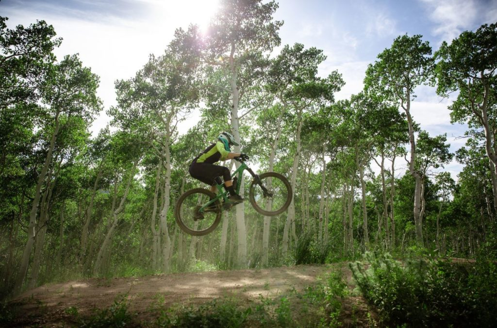 Side view of a mountain biker jumping off a jump