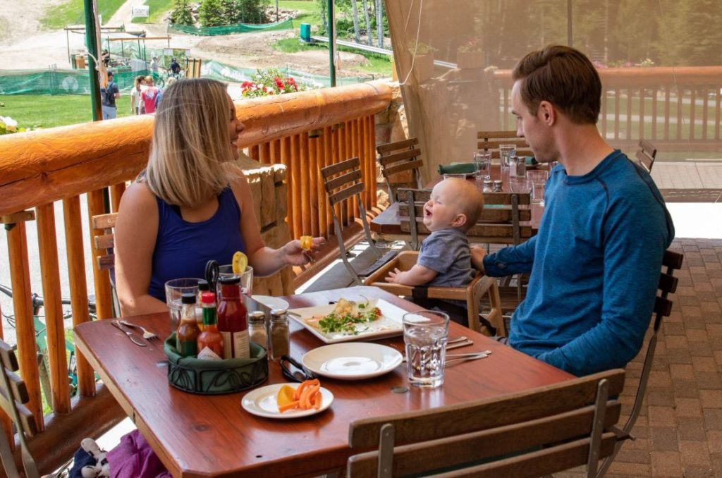 Family of three eating at a table in Park City Utah at Deer Valley