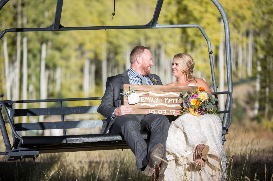 Fall wedding with bride and Groom sitting on a chairlift at Deer Valley Resort in Park City, Utah