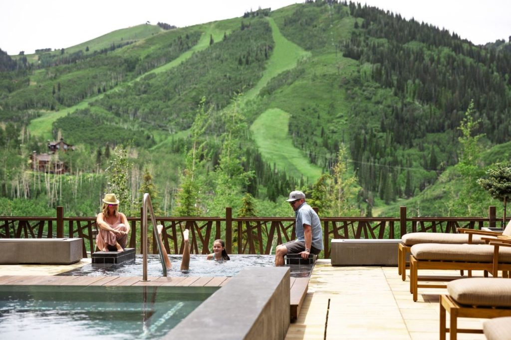 A family relaxing in a spa overlooking the mountains and ski runs.