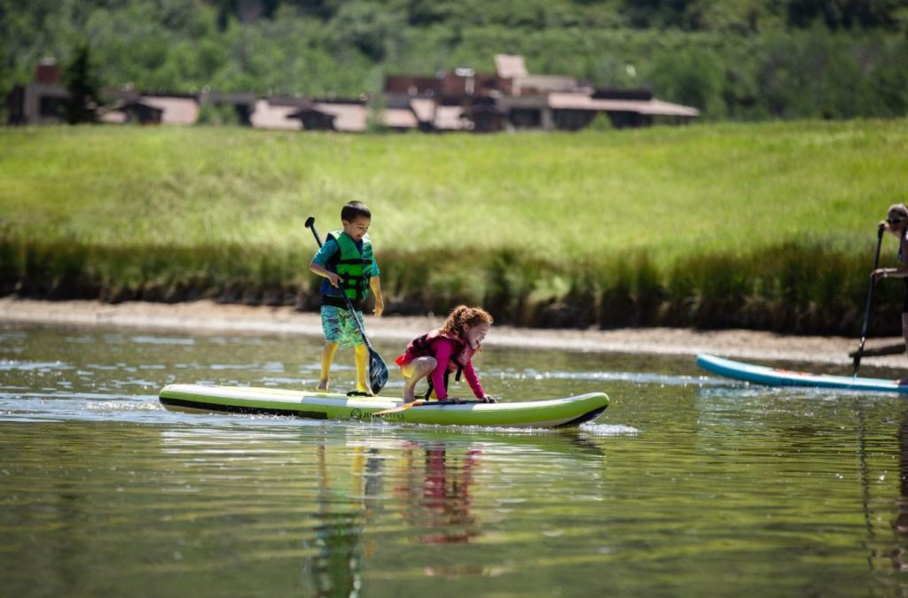 Two kids standup paddleboarding at Deer Valley Resort in Park City, Utah.