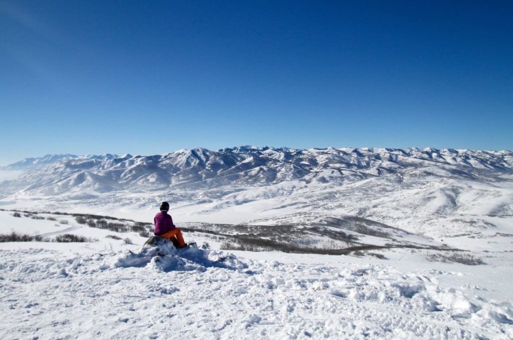 One person sitting on a rock looking out at Park city, Utah.