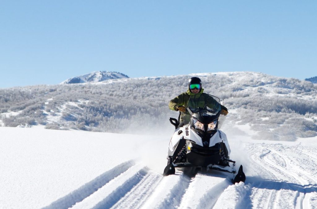 One Snowmobile with one person on it with a nice few